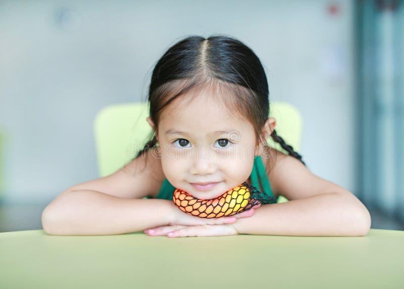 Entzückendes kleines asiatisches Kindermädchen, das Gummispielzeug im Kinderraum liegt und spielt stockbild