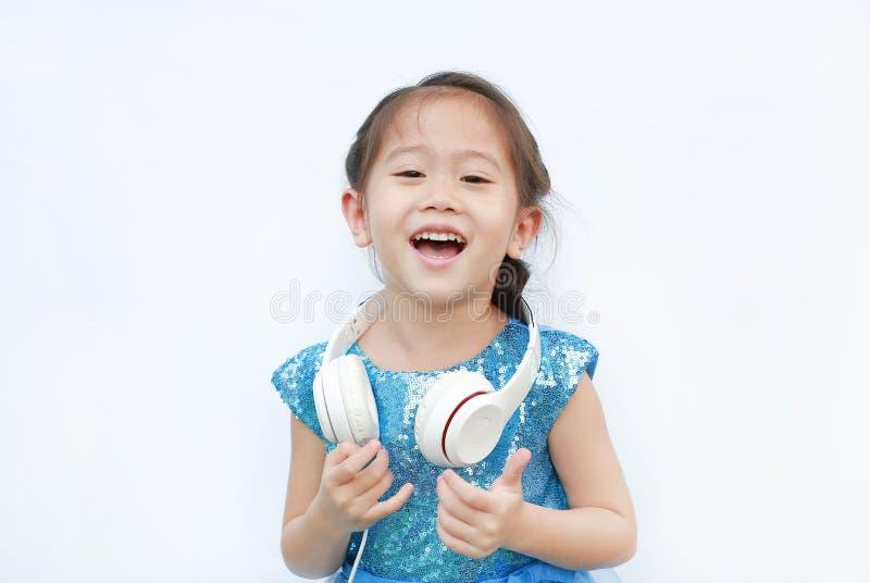 Entzückendes kleines asiatisches Mädchen in helles Kleiderhörender Musik mit den Kopfhörern lokalisiert auf weißem Hintergrund lizenzfreie stockfotografie