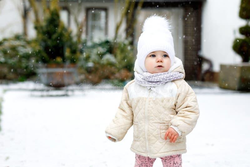 Entzückendes kleines Baby, das draußen erste Schritte im Winter macht Nettes Kleinkind, welches das Gehen lernt Kind, das Spaß au stockfotografie