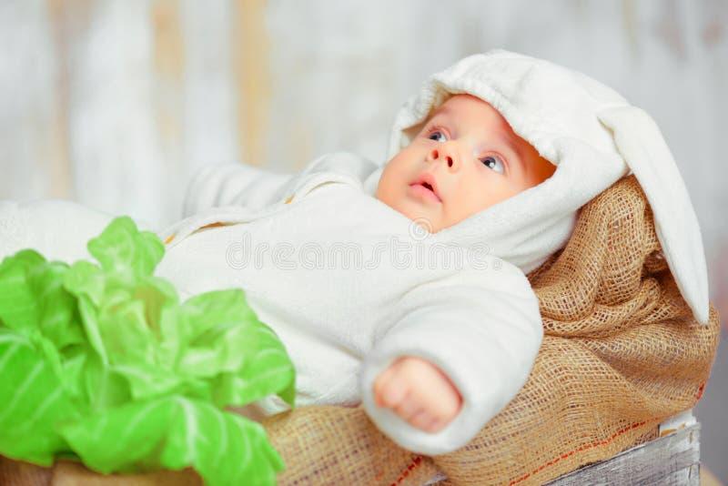 Entzückendes kleines Baby in einem lustigen Häschenbodysuit lizenzfreie stockfotos