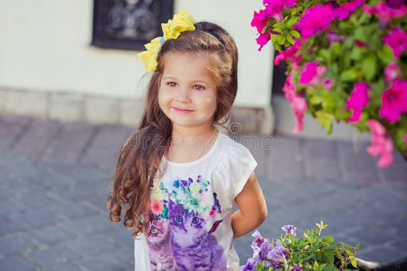 Entzückendes kleines Baby mit den kleinen Lippen des Schellfisches und den Brunettehaaren, die in Central Park trägt stilvolle we lizenzfreie stockfotos