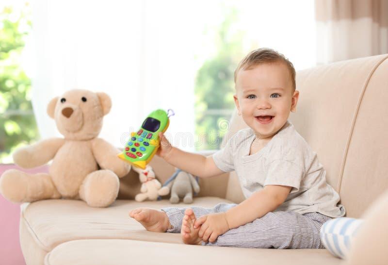 Entzückendes kleines Baby mit Spielzeugtelefon auf Sofa stockfotos