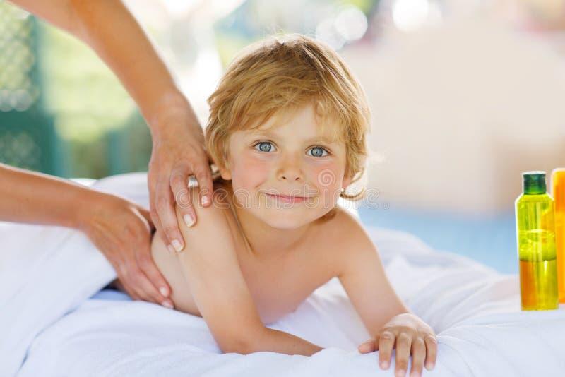 Entzückendes kleines blondes Kind, das im Badekurort mit Haben von Massage sich entspannt lizenzfreies stockbild