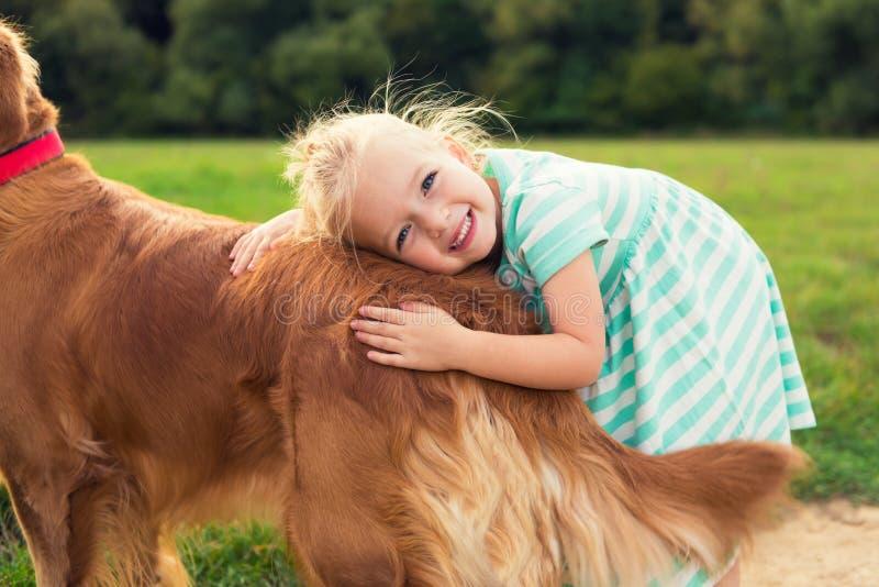 Entzückendes kleines blondes Mädchen, das ihren Hund umarmt stockbild