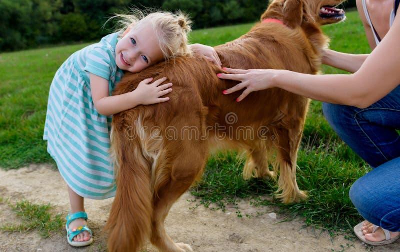 Entzückendes kleines blondes Mädchen, das ihren netten Schoßhund lächelt und umarmt stockfotografie