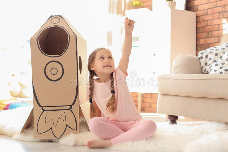 Entzückendes kleines Kind, das mit Papprakete spielt lizenzfreies stockfoto