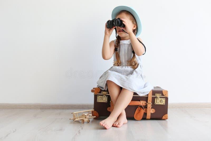Entzückendes kleines Kind, das Reisenden mit Koffer spielt stockbild