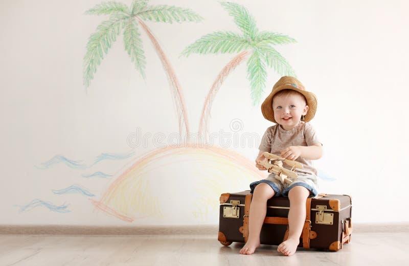 Entzückendes kleines Kind, das Reisenden mit Koffer spielt stockfotografie