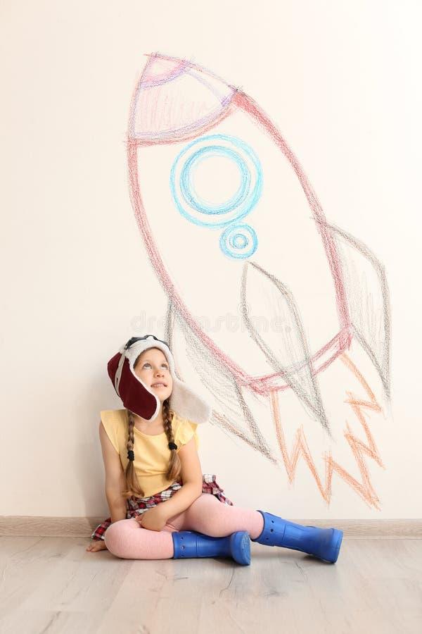 Entzückendes kleines Kind, das zuhause Astronautenwand mit Zeichnung des Raumschiffes spielt stockbilder