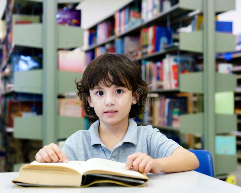 Entzückendes kleines Kind, Junge, sitzend in einer Bibliothek, Lesebücher lizenzfreies stockbild