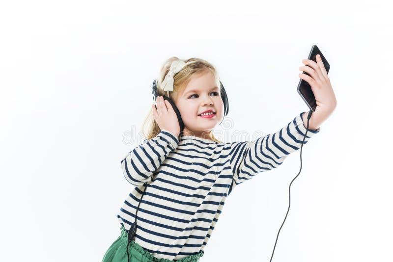 entzückendes kleines Kind mit den Kopfhörern, die selfie nehmen stockbild