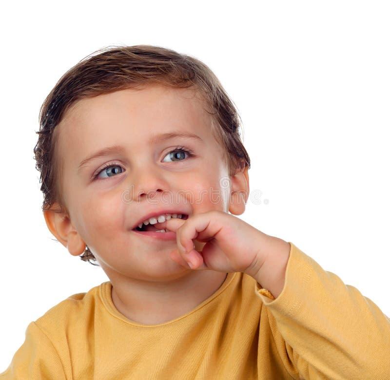 Entzückendes kleines Kind zwei Jahre alt, seine Hand saugend an lokalisiert lizenzfreies stockbild