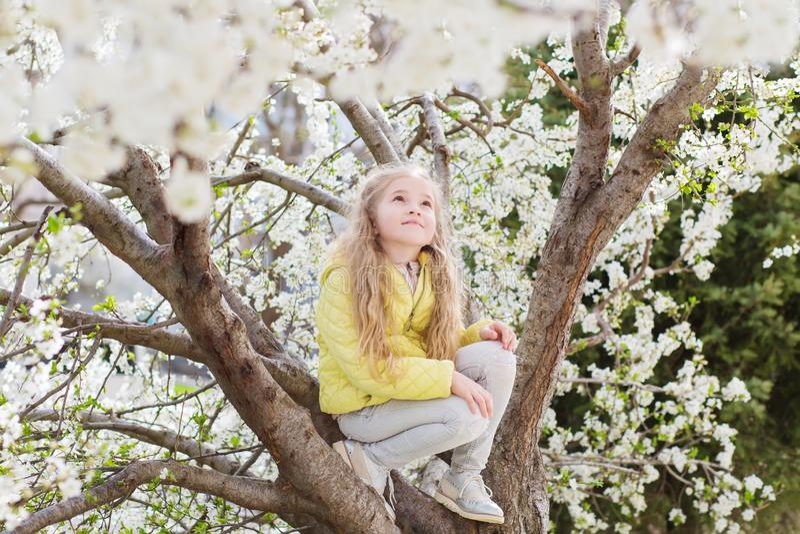 Entzückendes kleines Mädchen in blühendem Kirschbaumgarten am schönen Frühlingstag lizenzfreie stockfotografie