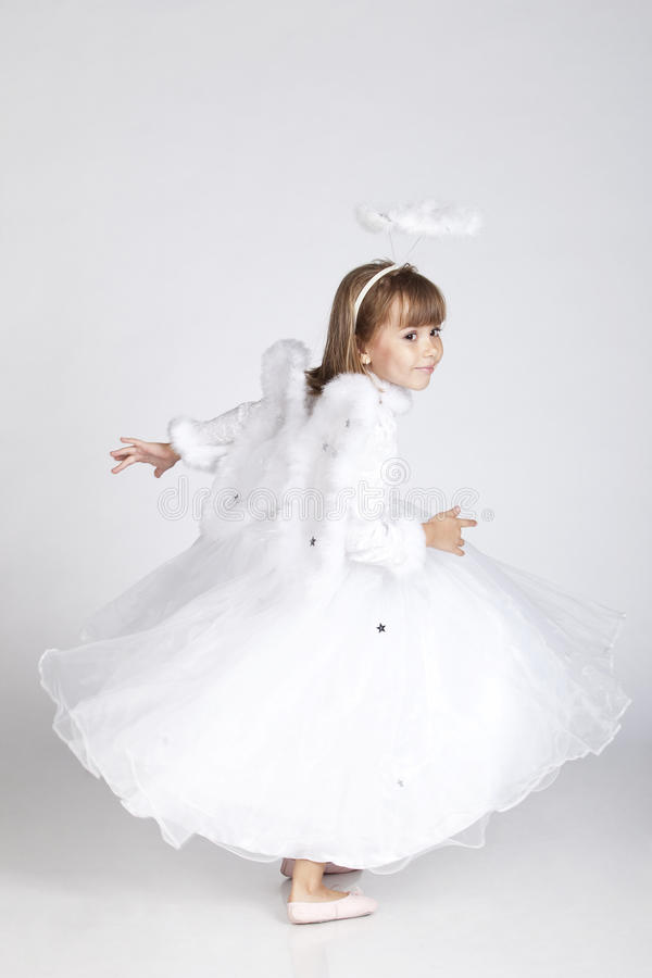 Entzückendes kleines Mädchen, das als Engelsflugwesen aufwirft lizenzfreies stockfoto