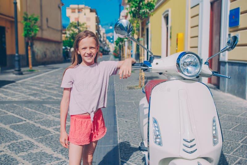 Entzückendes kleines Mädchen, das auf dem Trübsal geblasenen Freien lächelt stockbild