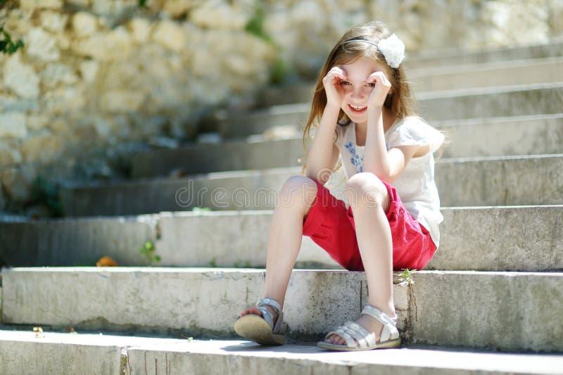 Entzückendes kleines Mädchen, das auf Treppe sitzt lizenzfreies stockbild