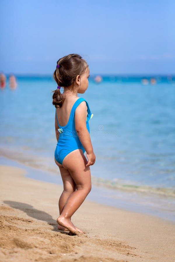 Entzückendes kleines Mädchen, das auf tropischem Strand steht lizenzfreie stockfotografie