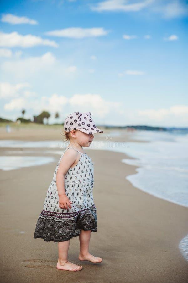 Entzückendes kleines Mädchen, das auf das Wasser auf dem Strand geht stockfoto