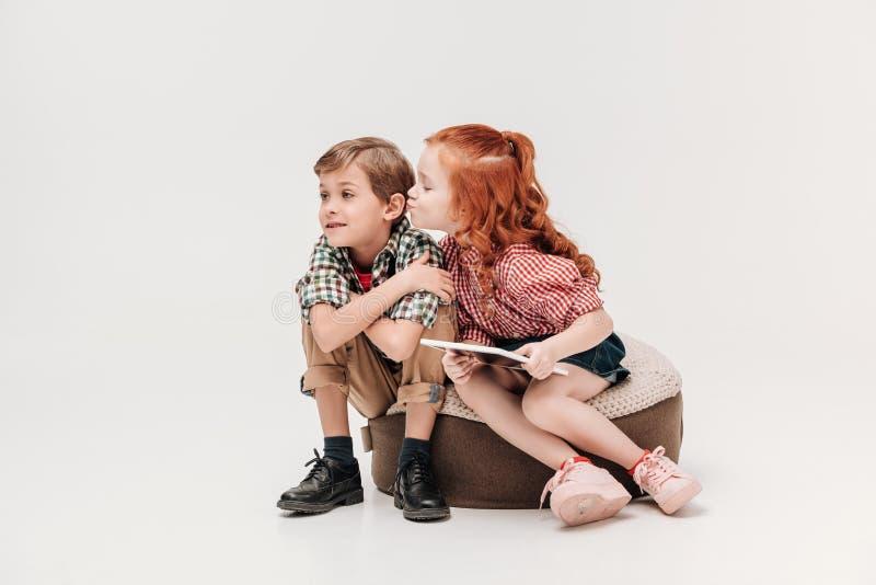 entzückendes kleines Mädchen, das digitale Tablette halten und fähig, kleinen Jungen zu küssen lizenzfreies stockbild