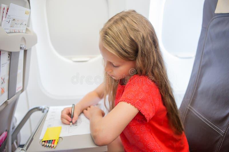 Entzückendes kleines Mädchen, das durch ein Flugzeug reist Scherzen Sie Zeichnungsbild mit den bunten Bleistiften, die nahe Fenst stockfoto
