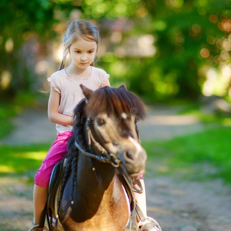 Entzückendes kleines Mädchen, das ein Pony reitet stockbilder
