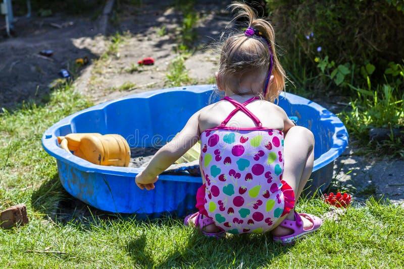 Entzückendes kleines Mädchen, das in einem Sandkasten spielt stockfoto