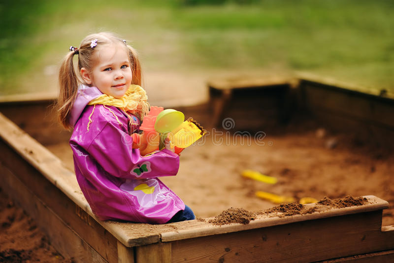 Entzückendes kleines Mädchen, das in einem Sandkasten spielt lizenzfreie stockfotos