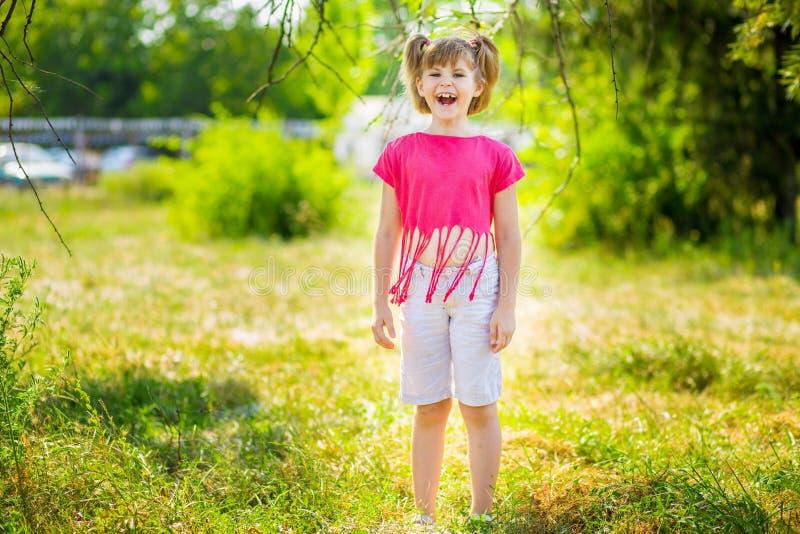Entzückendes kleines Mädchen, das in einer Wiese - glücklich lacht lizenzfreie stockbilder