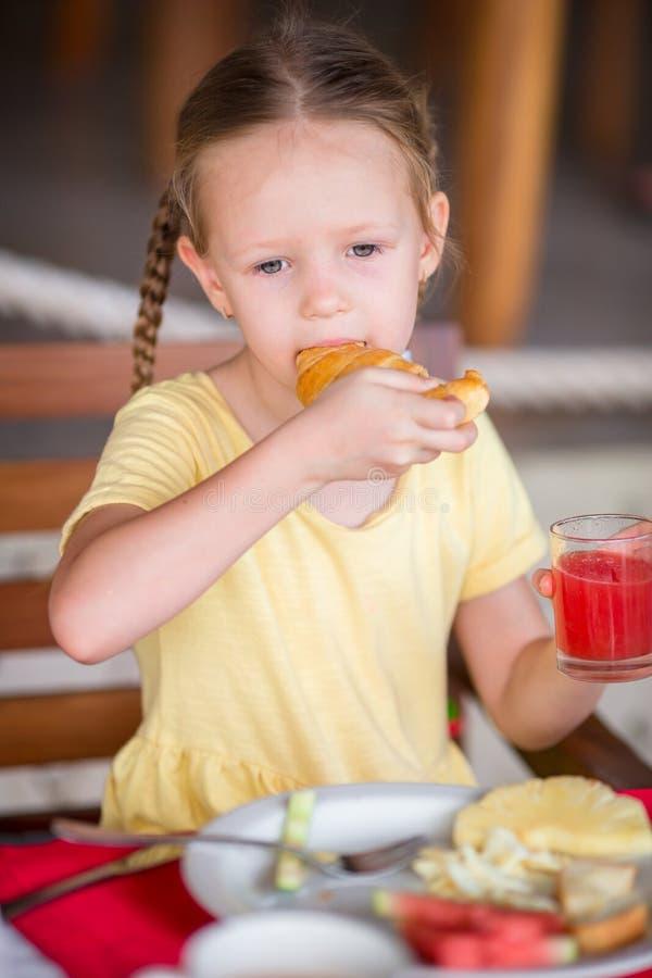 Entzückendes kleines Mädchen, das am Erholungsortrestaurant frühstückt lizenzfreie stockbilder