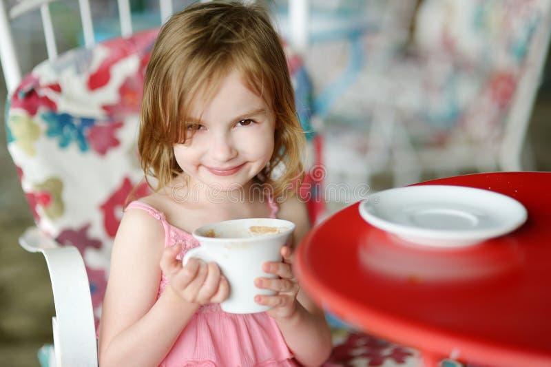 Entzückendes kleines Mädchen, das heiße Schokolade trinkt lizenzfreie stockfotos