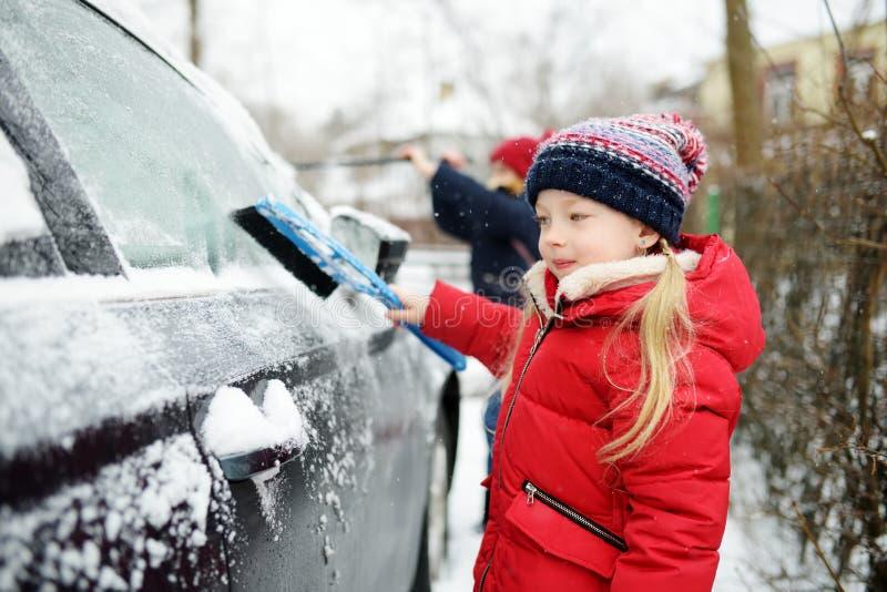Entzückendes kleines Mädchen, das hilft, einen Schnee von einem Auto zu bürsten Mama ` s kleiner Helfer lizenzfreie stockfotos