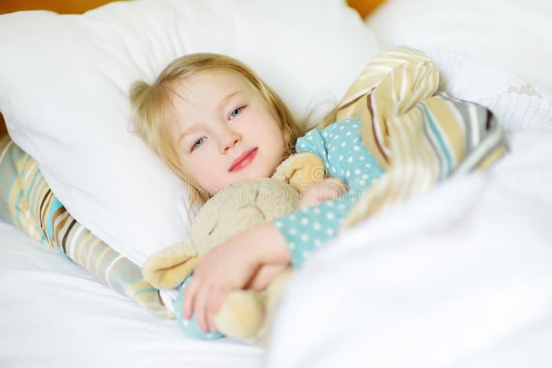 Entzückendes kleines Mädchen, das im Bett mit ihrem Spielzeug schläft Müdes Kind, das unter weiße Decke ein Schläfchen hält stockfoto