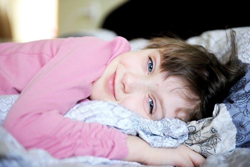 Entzückendes kleines Mädchen, das im Bett sich entspannt stockfoto