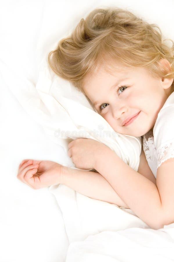 Entzückendes kleines Mädchen, das im Bett stillsteht lizenzfreie stockbilder