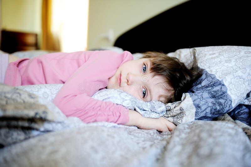 Entzückendes kleines Mädchen, das im Bett stillsteht stockfotos