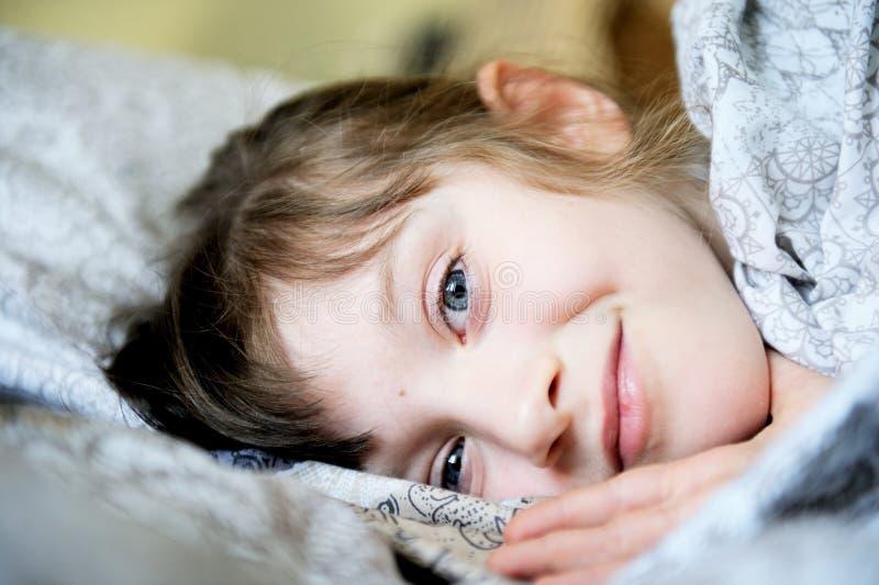 Entzückendes kleines Mädchen, das im Bett stillsteht stockbild