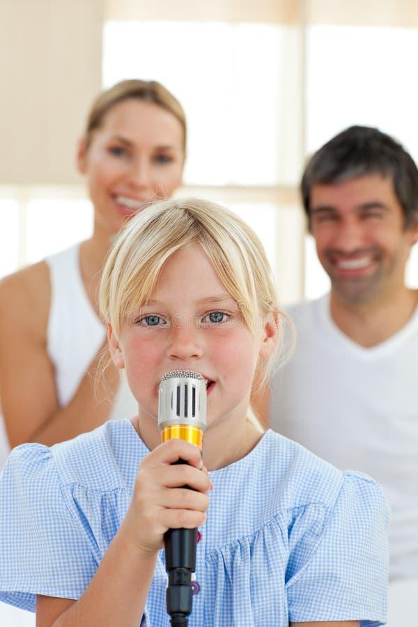 Entzückendes kleines Mädchen, das mit einem Mikrofon singt lizenzfreie stockfotografie