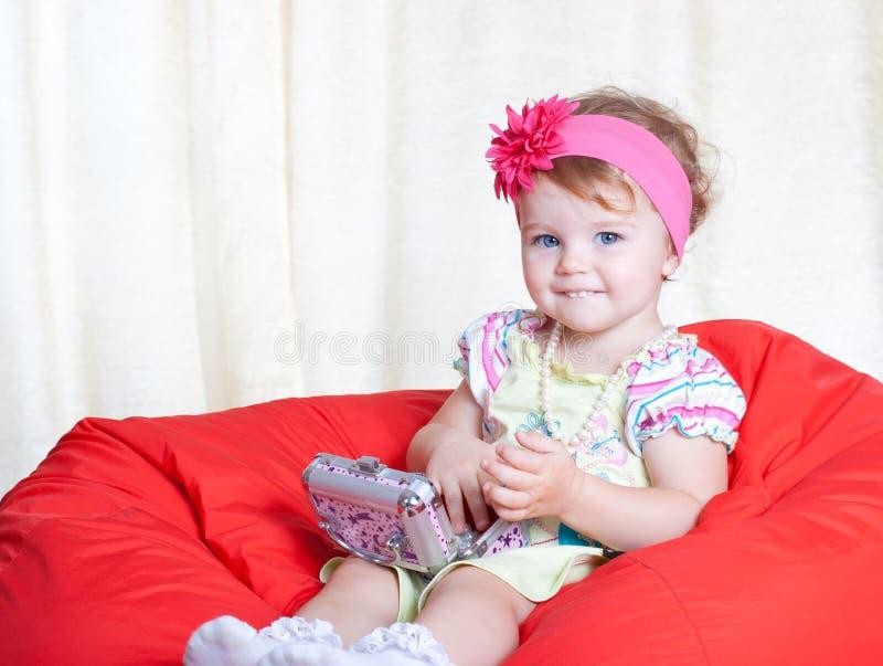 Entzückendes kleines Mädchen, das mit ihrem Kasten sitzt stockbild