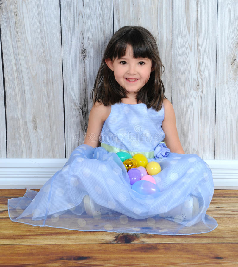 Entzückendes kleines Mädchen, das mit Ostereiern sitzt stockbild