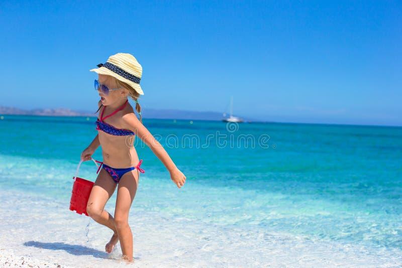 Entzückendes kleines Mädchen, das mit Spielwaren auf Strand spielt lizenzfreie stockbilder