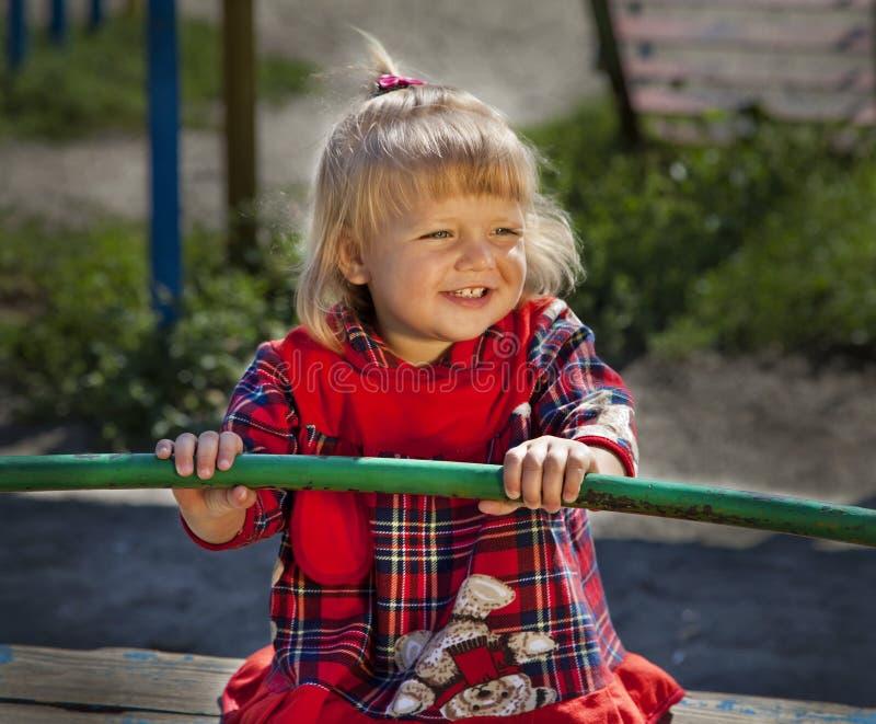 Entzückendes kleines Mädchen, das Spaß auf einem Schwingen hat stockfotos