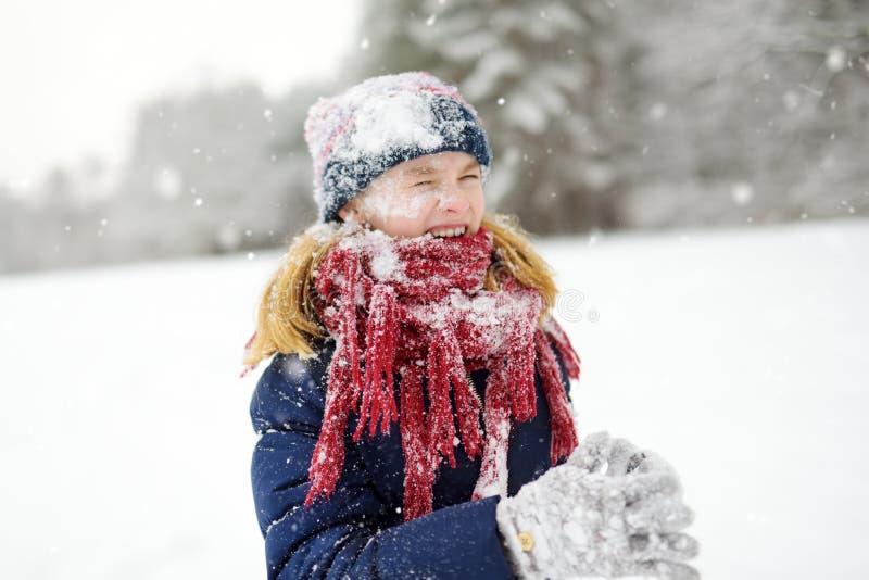 Entzückendes kleines Mädchen, das Spaß im schönen Winterpark hat Nettes Kind, das in einem Schnee spielt stockbilder