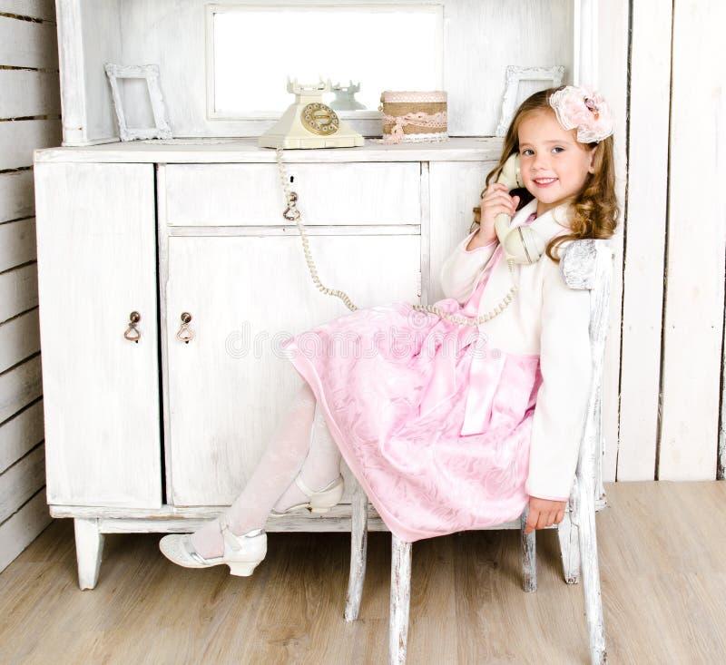 Entzückendes kleines Mädchen, das telefonisch im Weinleseinnenraum sreaking ist stockfoto