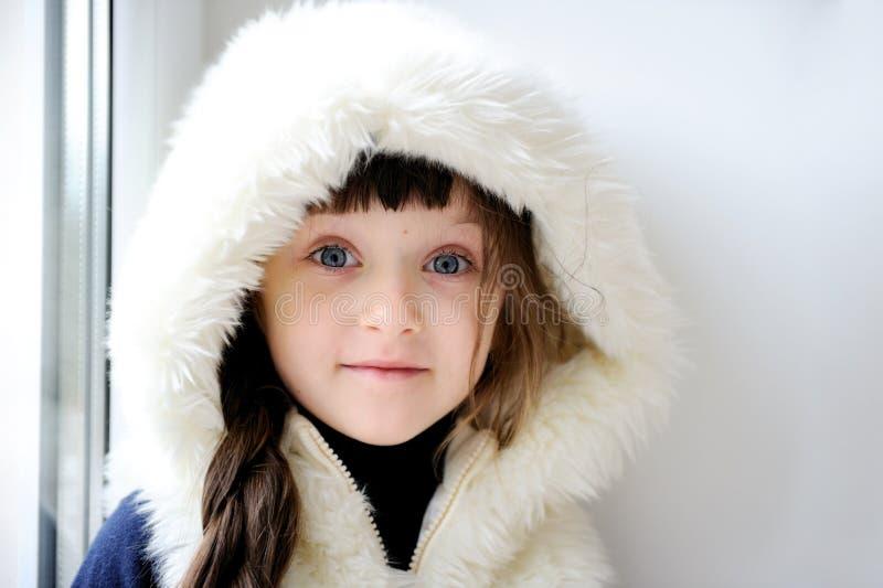 Entzückendes kleines Mädchen in der weißen Pelzhaube stockfoto