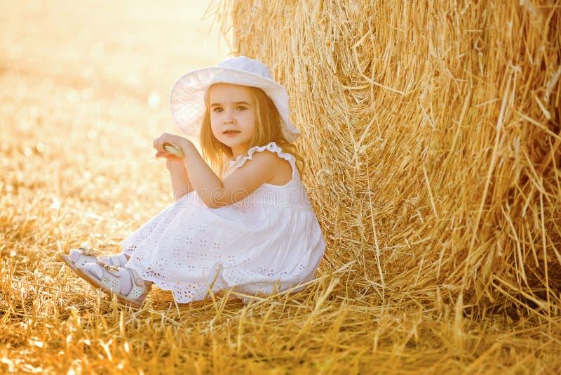 Entzückendes kleines Mädchen in einem weißen Kleid und in einem weißen Hut ist sittin eingeschaltet lizenzfreie stockbilder