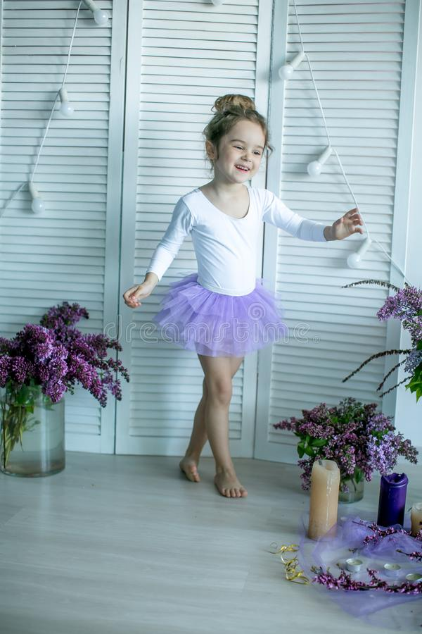 Entzückendes kleines Mädchen gekleidet als Ballerina in einem Ballettröckchen, ihre Ballettpantoffel binden stockbilder