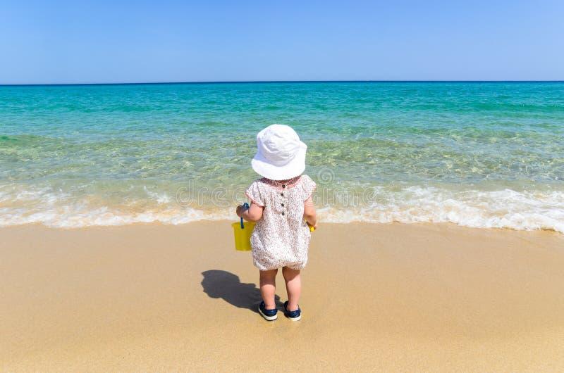 Entzückendes kleines Mädchen im Badeanzug, der Spaß am tropischen sandigen Strand hat stockbilder