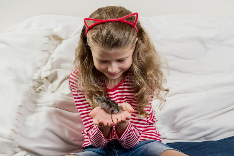 Entzückendes kleines Mädchen mit ihrem Haustier - kleiner Hamster stockfotografie