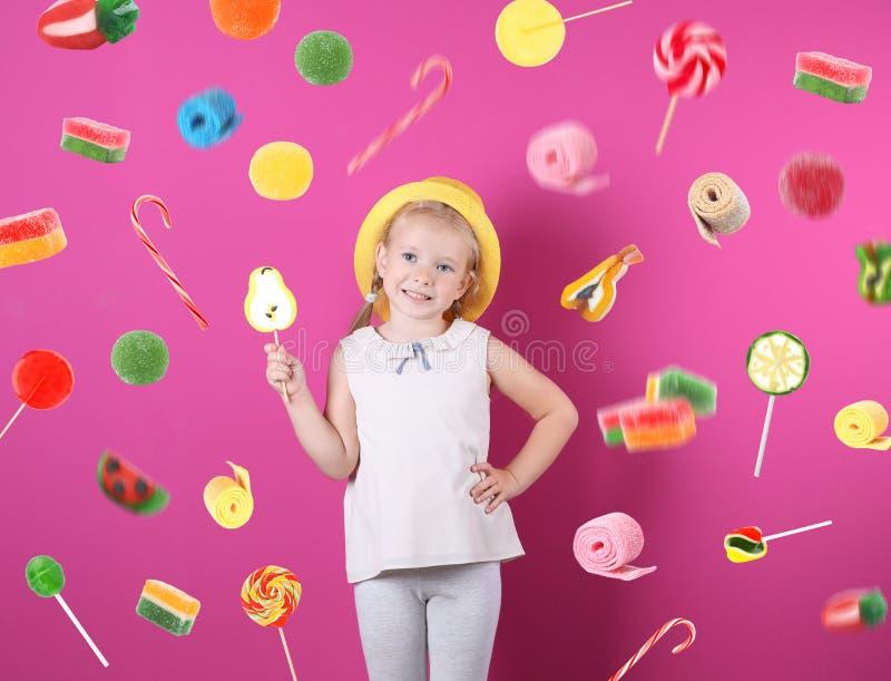 Entzückendes kleines Mädchen mit lollypop und fliegende Süßigkeiten auf Hintergrund stockfotografie