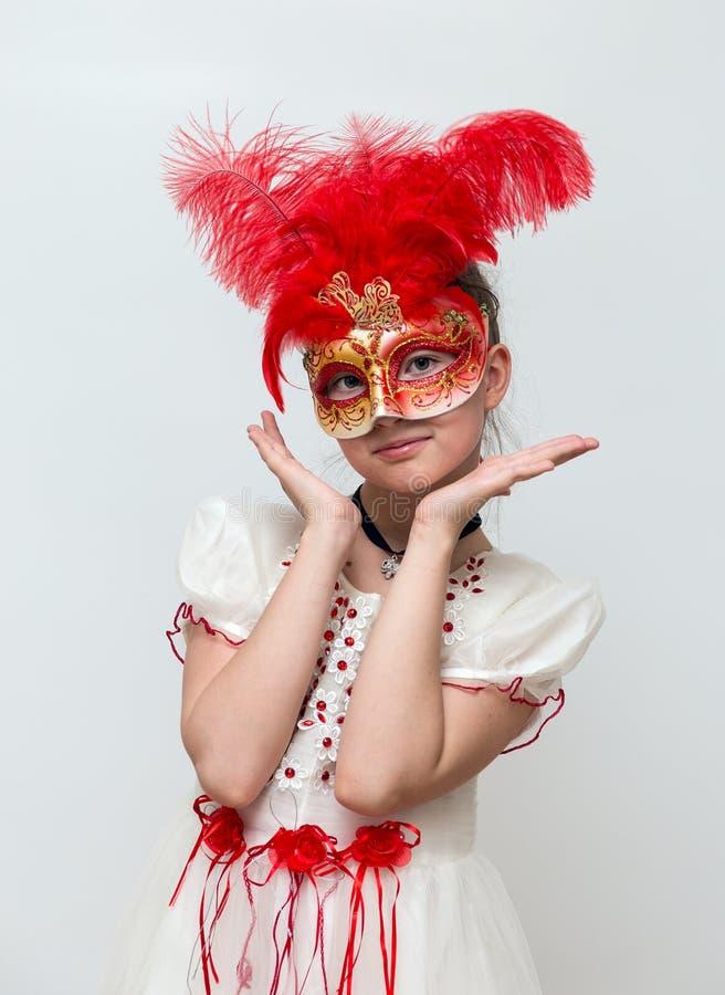 Entzückendes kleines Mädchen mit venetianischer Karnevalsschablone lizenzfreies stockbild